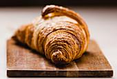 Frisch gebackenes Croissant auf Schneidebrett