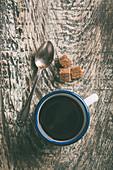 Schwarzer Kaffee in Emaillebecher daneben Vintagelöffel und Würfelzucker