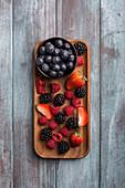 Frische Beeren im Schälchen und auf Servierplatte aus Holz (Aufsicht)