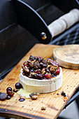 Grilled camembert with grapes and nuts on a wooden board
