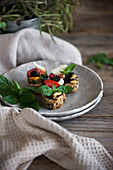 Crostini with mozzarella, olives, mussels, tomatoes, and basil leaves