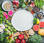Stillleben mit Gemüse, Obst, Samen, Getreide, Gewürzen, Superfoods und Kräutern um einen weissen Teller