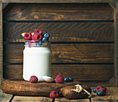 Glass jar of white yogurt with fresh garden berries and peach on serving board over rustic table