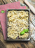 Various homemade fresh uncooked Italian pasta with flour and green basil leaves in wooden tray
