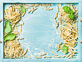 Various homemade fresh uncooked Italian pasta with flour and green basil leaves in blue wooden tray