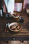 Gegrillte Rippen und Würstchen mit Rotwein auf rustikalem Holztisch