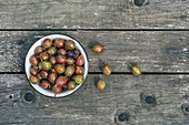 Bowl of ripe gooseberries on a wooden surface