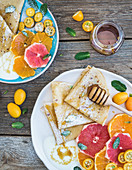 Spring vitamin breakfast set - Thin crepes or pancakes with fresh grapefruit, orange, kumquat, honey, cream and mint leaves