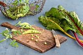 Pea pods on a wooden board next to colourful chard stems