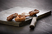 Dried figs on a wooden board with a peeler