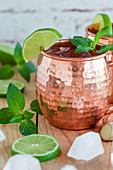 A Moscow Mule in a copper mug with mint and lime