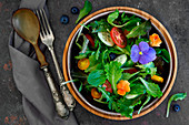 Spring salad, with different leaves, various type of tomatoes, cucumber and edible flowers