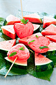 Heart-shaped watermelon popsicles on slices of watermelon