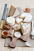 Various types of cheese from the Emilia Romagna region on a wooden chopping board