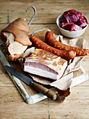 Various types of sausages and meat on a cutting board