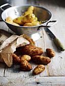 Gewaschene Kartoffeln im Sieb und ungewaschene auf Holztisch