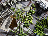 Green beans and Brussels sprouts surrounded by old black-and-white photos