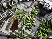 Grüne Bohnen und Rosenkohl, umgeben von alten schwarz-weiß-Fotos