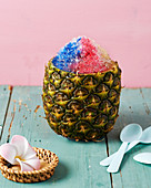 A pineapple filled with flower petal granita