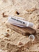 Plastikflasche als Strandgut im Sand mit Zettel und Aufschrift 'please recycle me'