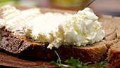 Brotscheibe mit Frischkäse bestreichen