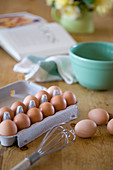 Eggs in egg carton and baking utensils on wooden table