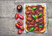 Rustic tomato autumn pie with fresh basil, thyme and tomatoes on a silver tray over a sackcloth background