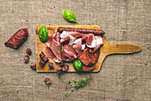 Meat selection: wine set on a rustic wood board over a rough sackcloth background