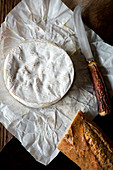 A whole Camembert cheese from above on its wrapper with a horn handled cheese knife and baguette