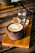 A cappucino in a rustic earthenware cup on a wooden board with a glass of water and sugar