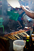 Satay sticks on the grill being fanned at a market in Bali