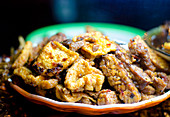 A close up of Balinese Tempeh and fried Tofu with chili