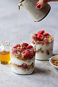Yogurt and granola parfait with raspberries and honey