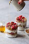 Schichtdessert mit Joghurtparfait, Granola, Himbeeren und Honig