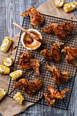 Frittierte Chicken Wings mit BBQ-Sauce und Maiskolben (Aufsicht)