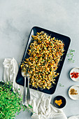 Spicy sprouted lentils with corn served on a black rectangular plate with a spoon and a fork on the side