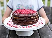 Schokoladenbiskuittorte mit Ganache, Karamellsauce und getrockneten Himbeeren auf Tisch im Freien