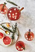 Pink Grapefruit Mocktail mit Rosmarin in Karaffe und Gläsern (Aufsicht)