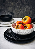 Fresh persimmon in a bowl on a marble background