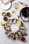 Geöffnete Austern auf Eis serviert mit verschiedenen Dips und Champagner