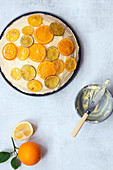 A round orange cake spread with butter icing and decorated with slices of candied lemon, lime and orange