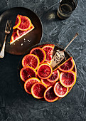 Moody blood orange cake with slices of poached blood oranges on top in a sugar syrup