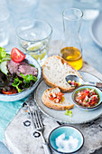 A mixed leaf salad with beef fillet and tomatoes, baguette with tomato chutney