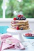 A pancake cake with fresh blackberries, raspberries, cherries and blueberries