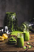 Freshly mixed green smoothies in screw-top jars with a blender in a background