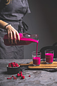 A woman pouring a pink smoothie from a carafe into glasses