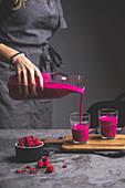 Frau giesst pinkfarbenen Smoothie aus Karaffe in Gläser