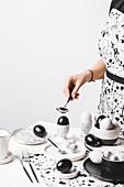 Frau mit Schürze vor Tisch gedeckt in Schwarz-Weiss mit gefärbten Eiern