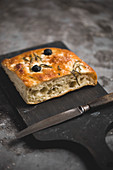 Focaccia with olives and rosemary on a wooden board