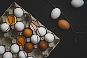 A egg box with white and brown hen's eggs, whole and cracked